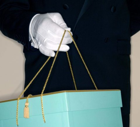 Doorman holding gift box, mid section